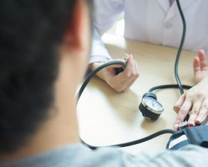 Doctor checking  patient arterial blood pressure.